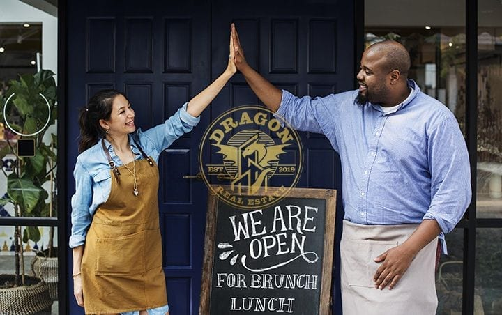 business owners standing with open blackboard